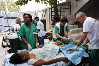 52722                     Carrefour, OCA surgery makeshift area outside the building of the Carrefour hospital. Patient with 2 broken legs. Haitian doctor Adesca, Surgeon Paul McMaster and German nurse Anja Wolz