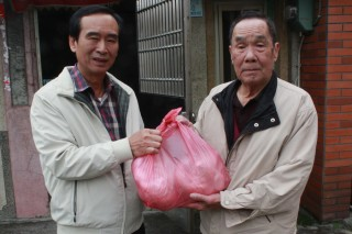 壯圍鄉公所秘書沈清山(左)代表公所發放春節慰問物資。〔圖/記者張淑玲攝〕
