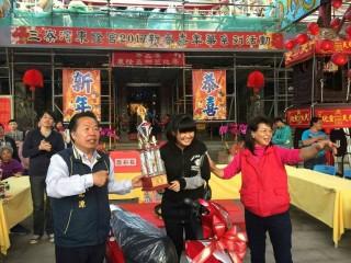 高雄市黃汎玉小姐(中)擲筊挑戰賽獲得冠軍獎125cc機車,相當高興,左為總幹事吳崑源。(記者邱仁武/攝)