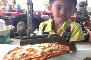 哇~好香又好吃港東披薩出爐,小朋友要提起等裝進紙盒時手還會發抖,直叫阿嬤要動作快點!(記者/黃芳祿攝)