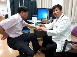 吳輝雄醫師(右)進行磁力貼療法對下背痛療效之研究。(記者許素蘭/攝)