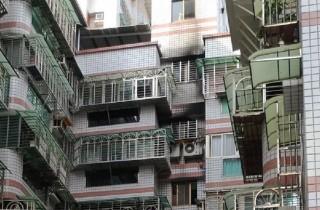 板橋公寓冷氣自爆著火,大樓牆面已經明顯被燻黑,冷氣機上方遮雨棚被燒出一個大洞。(圖/記者陳建富攝)