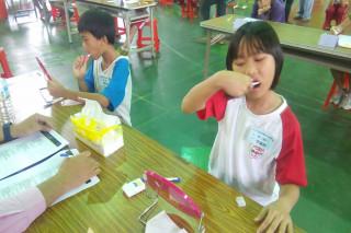 國小口腔保健潔牙觀摩活動在新營區新民國小活動中心登場,小朋友使用牙刷清潔牙齒。(圖/記者黃芳祿攝)