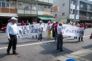 學甲民眾持「抗議殺人兇手電磁波」白布條走上街頭。左一為臺南市議員謝財旺。(圖/記者黃芳祿攝)