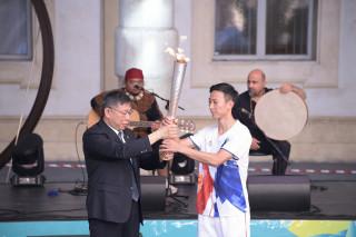 台灣火炬手、奧運金牌選手朱木炎,從台北市長柯文哲手中接下火炬。(圖/台北市政府提供)