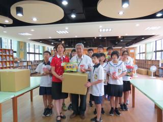 教育局長高安邦頒贈食品物資提供學生,使愛心午餐發揮最大的效益。