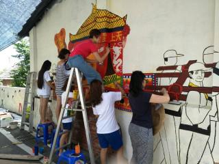 墨西哥、香港、大陸及台灣計十二位國際青年志工,為台中大安區頂  安社區陳舊的牆壁上,繪畫出最具鄉土性的大甲媽祖遶境進香隊伍圖  ,人物及陣頭活動栩栩如生。(記者陳榮昌攝)