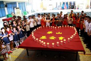 來賓們與同學點亮心燈宣示讓愛傳承。(記者扶小萍攝)