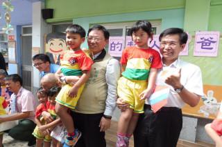 教育部長潘文忠(右一)抱著學童說,政府預計在四年內增設1247所非營利幼兒園。(圖/記者黃芳祿攝)
