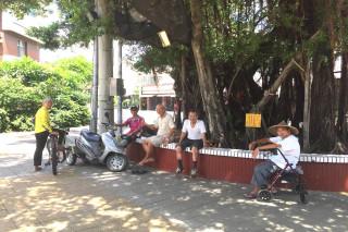 酷熱中找消暑。台南沿海北台南佳里建南里九龍殿百年老樹下,在這波熱浪中聚集納涼民眾,他們說樹蔭下乘涼比吹冷氣還舒服。(圖/記者黃芳祿攝)