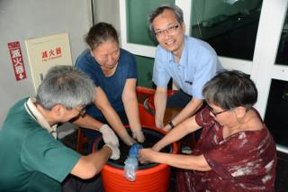 彰化生活美學館館長尹彙武(右)與阿公阿嬤體驗藍染DIY