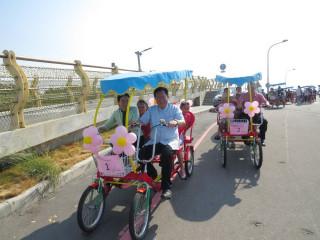桃園市長鄭文燦在「新屋傳愛幸福家庭向前行」活動中,與立法委員陳賴素美一起踩動親子三輪車搭載小朋友。