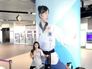 世大運跆拳道品勢混合團體項目金牌得主蘇佳恩與自己的環型形象照合影。