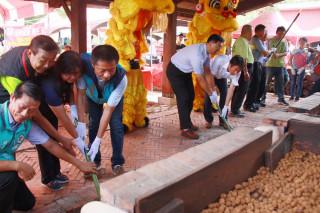 來賓為龍眼起灶點火展開文化季活動。(記者扶小萍攝)