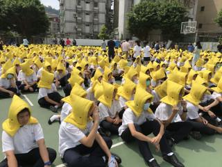 中學生頭戴防災頭套至操場疏散
